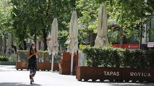 Una joven pasea con la Rambla de Catalunya, donde las terrazas permanecen cerradas.
