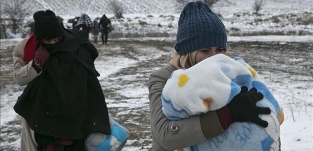 Una mujer migrante protege a su hijo con una manta mientras camina cerca de Miratovac (Serbia), este lunes.