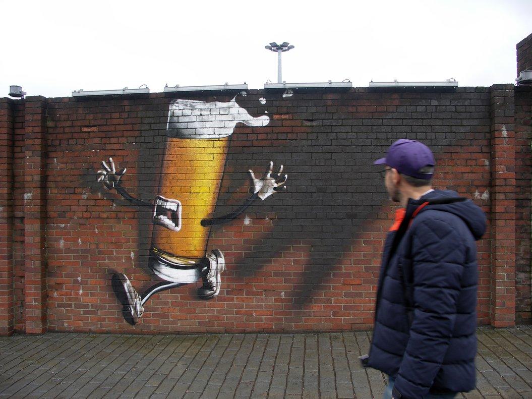 Uno de los muros que rodean la fábrica de Tennent's, decorados con grafitis cerveceros.
