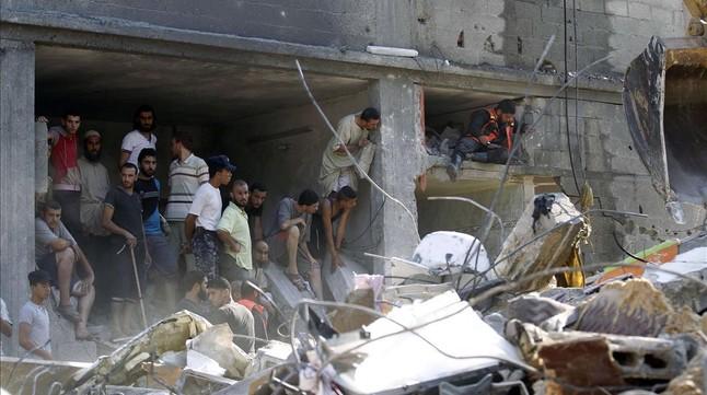 Varios palestinos miran la casa destruida donde han muerto los mandos de Hamás.