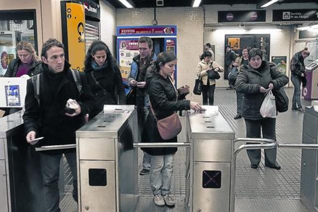 Varios usuarios entran en una estación del metro de Barcelona validando sus títulos de transporte.