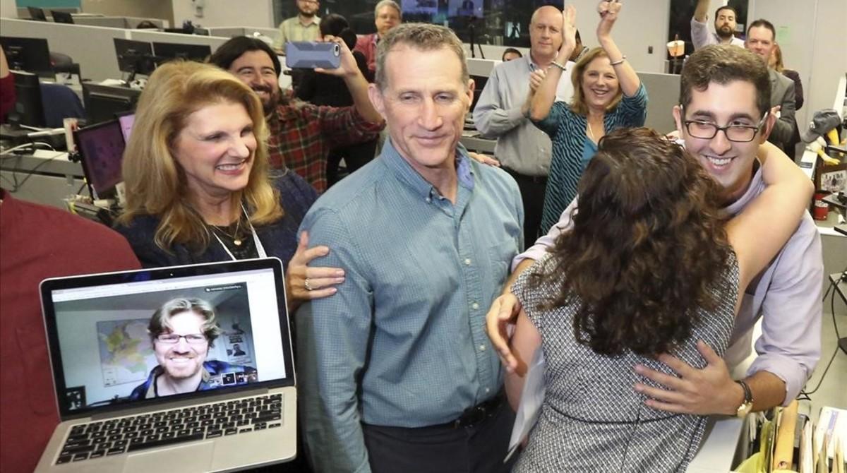 El periodista del Miami Herald Nicholas Nehamas (derecha) recibe un abrazo de la directora ejecutiva Aminda Marques Gonzalez, mientras Jim Wyss observa vía Skype desde Bogotá, tras escuchar que han recibido el premio Pulitzer por los papeles de Panamá.