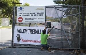 Pancarta de las autoescuelas en la que reclaman poder trabajar, en el Sot del Migdia de Barcelona, este lunes.
