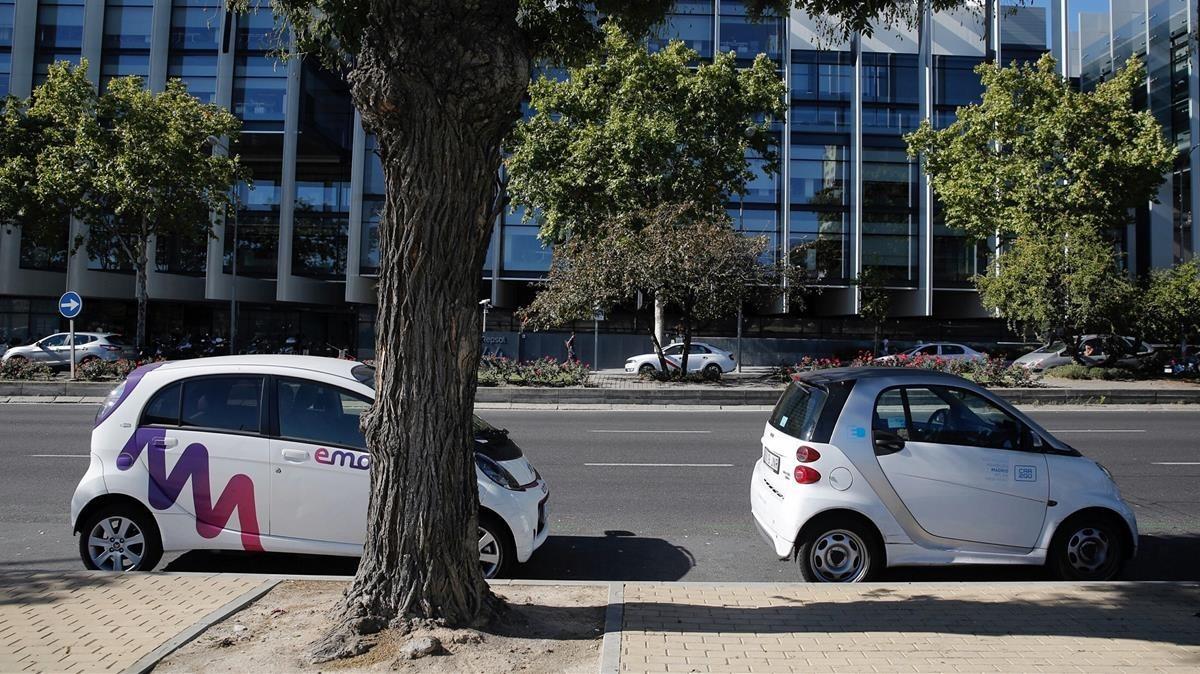 Dos coches de las compañías Emov y Car2go aparcados en Madrid.