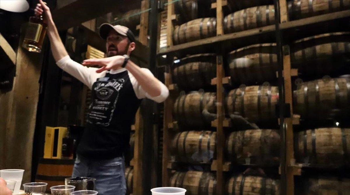 Un guía de Jack Daniel's explica unode los whiskis de la marca durante una cata para un grupo de visitantes.