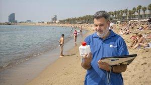 Fidel Picó, técnico de la ACA, con el agua recogida este jueves en la playa del Somorrostro de Barcelona.