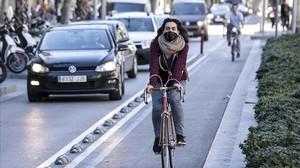 Una ciclista circula por el carril bici de Diagonal protegida por una mascarilla antipolución