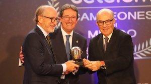 Antonio Brufau recibe el Casco de Oro de manos de Carmelo Ezpeleta, organizador del Mundial de motociclismo, y Manuel Casado, presidente de la Federación Española de Motociclismo.