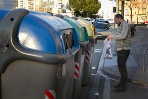 Un ciudadano utiliza un conjunto de contenedores de reciclaje en una calle de Barcelona.