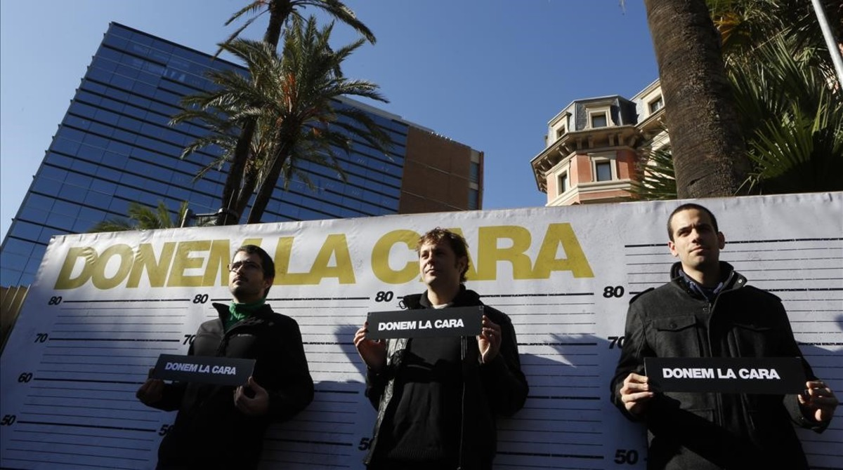 Los tresdetenidos, junto a una pancarta con ellema Damos la cara.