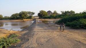Un hombre regresa con dos bidones llenos después de ir al río a coger agua con su bicicleta en Lodwar, en Kenia.