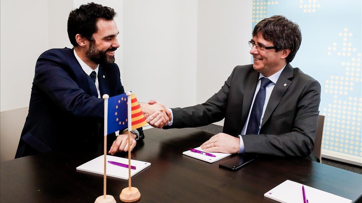 El expresidente de la GeneralitatCarles Puigdemontestrecha la mano del presidente del Parlament, Roger Torrent, durante la reunión que ambos han mantenido este miércoles en Bruselas.