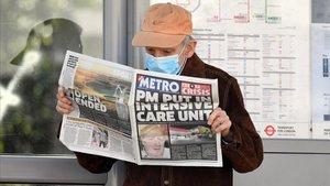 Un hombre protegido con una mascarilla lee un diario donde se informa del ingreso hospitalario de Boris Johnson por coronavirus.