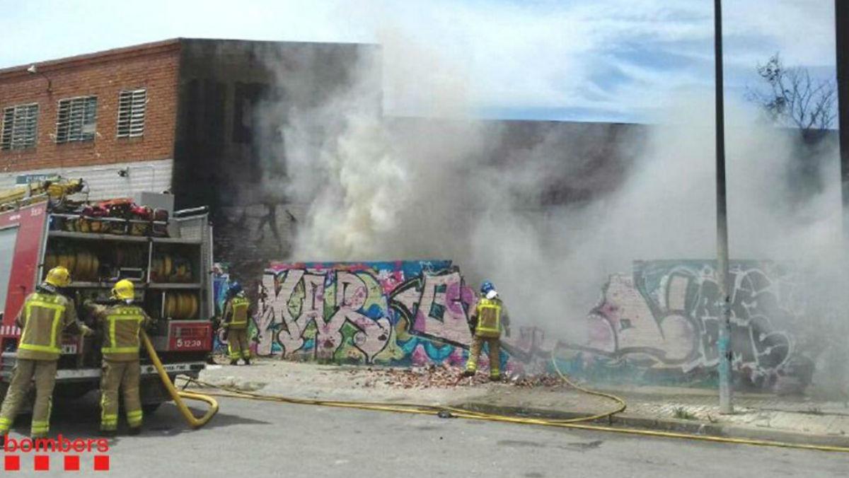 Los bomberos extinguen el fuego que se ha originado en un patio industrial de LHospitalet de Llobregat.