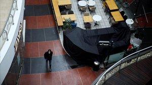 Un israelí con máscara en un centro comercial vacío.