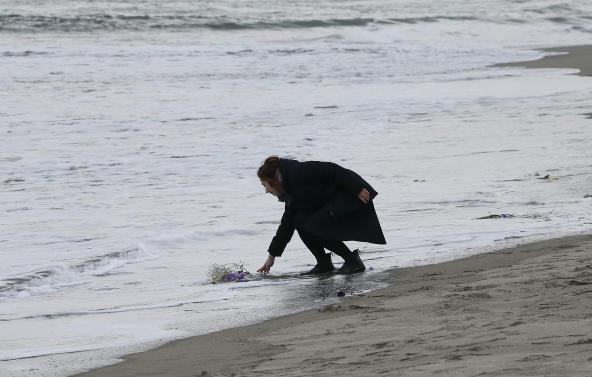 KMA38 UKEDO (JAPÓN) 11/03/2016.- Mark Kanekita, de 37 años, lanza flores al mar en memoria de las víctimas del terremoto y posterior tsunami de hace cinco años en el distrito de Abraham en Sendai (Japón) hoy, 11 de marzo de 2016. Japón recordó hoy con un minuto de silencio el terremoto y el tsunami acaecidos hace justo cinco años, que dejaron más de 18.000 muertos y desaparecidos en el noreste de Japón y provocaron el accidente nuclear de la central de Fukushima. En los diversos actos celebrados por todo el país se guardó un minuto de silencio a las 14.46 hora local (05.46 GMT), momento exacto en el que el 11 de marzo de 2011 se registró el terremoto de 9 grados en la escala abierta de Richter que desencadenó la tragedia. EFE/Kimimasa Mayama