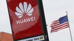 Logotipo de Huawei y la bandera de EEUU de fondo en Kuala Lumpur, Malasia.