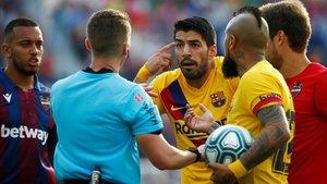 Los jugadores del Barça rodean al árbitro en el partido ante el Levante.