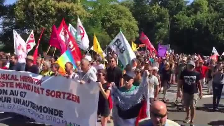 Distintos momentos de la manifestación que ha recorrido este sábado diversas calles de Hendaya e Irún en protesta por la celebración de la cumbre del G7.
