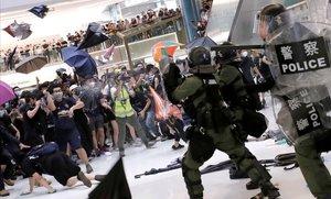 Manifestantes lanzan paraguas contra policías antidisturbios en un centro comercial de Hong Kong.