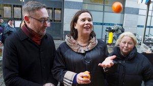 Mary Lou McDonald lanza una naranja al aire durante una visita a un puesto de fruta callejero en Dublín, este lunes.