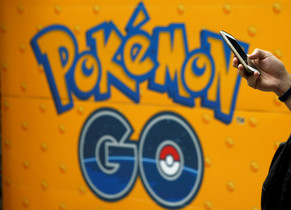 Un joven juega a Pokémon Go frente a un anuncio promocional de la aplicación.