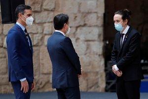 El presidente del Gobierno, Pedro Sánchez, y el primer ministro italiano, Giuseppe Conte, saludan al vicepresidente segundo, Pablo Iglesias, durante la recepción en el patio de honor del palacio de la Almudaina, donde se celebró este 25 de noviembre la XIX Cumbre bilateral España-Italia.