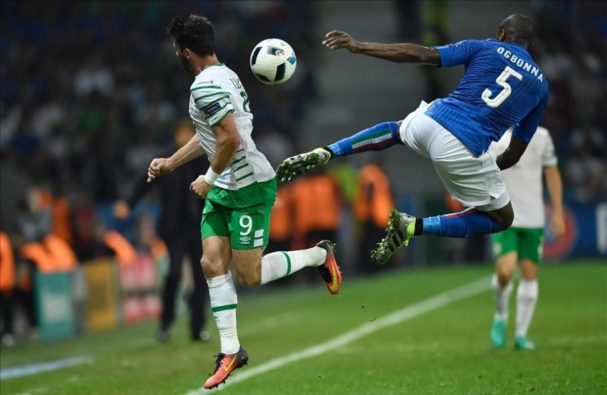 Shane Long y Angelo Ogbonna compiten por el balón durante el partido de laEurocopa 2016 entre Italia e Irlanda.
