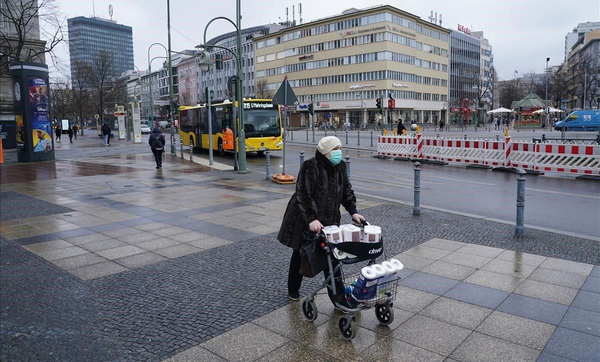 Una anciana con una máscara protectora empuja un carrito cargado de papel higiénico y toallas de papel, este lunes, en Berlín.