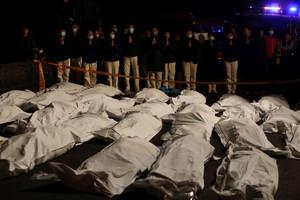 Voluntarios rezan ante los cadáveres de los fallecidos en el accidente de autobús en Taiwán.