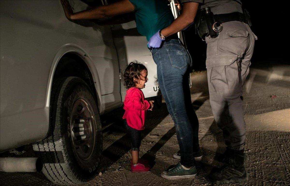 Yana, de Honduras, llora mientras su madre, Sanda Sánchez, es registrada por un agente fronterizo en McAllen, Texas, Estados Unidos.