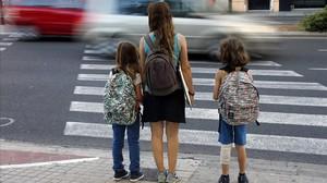 Una mujer acompaña a dos niñas al colegio en València.