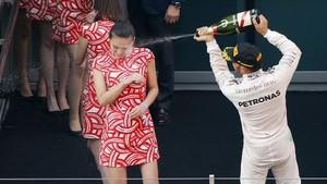 Lewis Hamilton rocía con champán la cara de una mujer durante la celebración de su victoria en el Gran Premio de Shanghái de Fórmula 1, en el 2015.