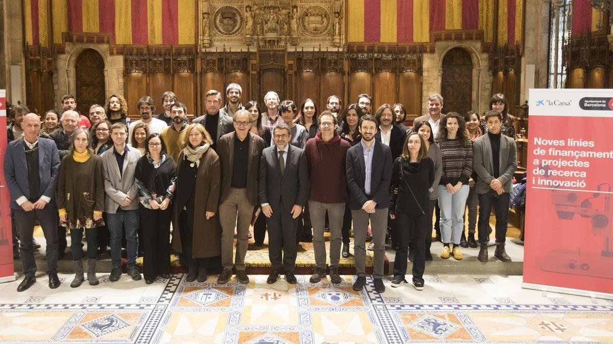 En el centro,Joan Subirats, teniente de alcalde de Cultura, Educación, Ciencia y Comunidad, y Ángel Font, director corporativo deInvestigación y Estrategia de Fundacióla Caixa, con los investigadores seleccionados en elPla Barcelona Ciència, este viernes en el Ayuntamiento de Barcelona.