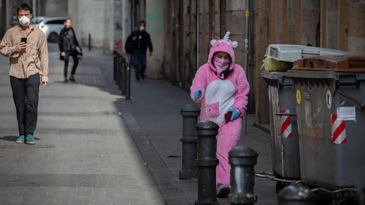 Una mujer con un traje de unicornio y protegida con mascarilla y guantes en Barcelona.