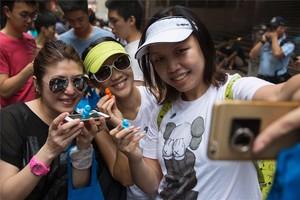 Tres jóvenes se hacen un selfi en Hong Kong.