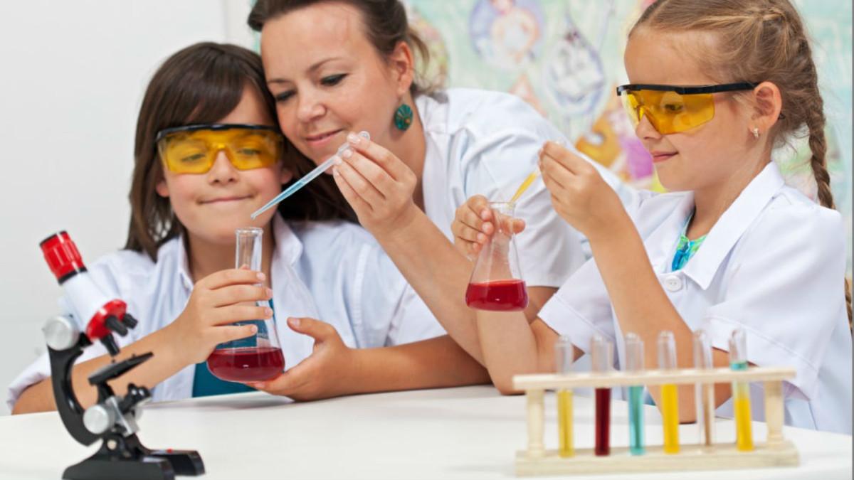 Una mujer y dos niñas realizan experimentos científicos