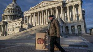 El activista antri-Trump,Stephen Parlato, pasa frente al Capitolio con un cartel con la foto del presidente.