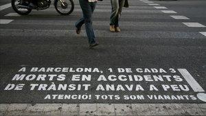 Aviso para peatones sobre la calzada en una calle de Barcelona.