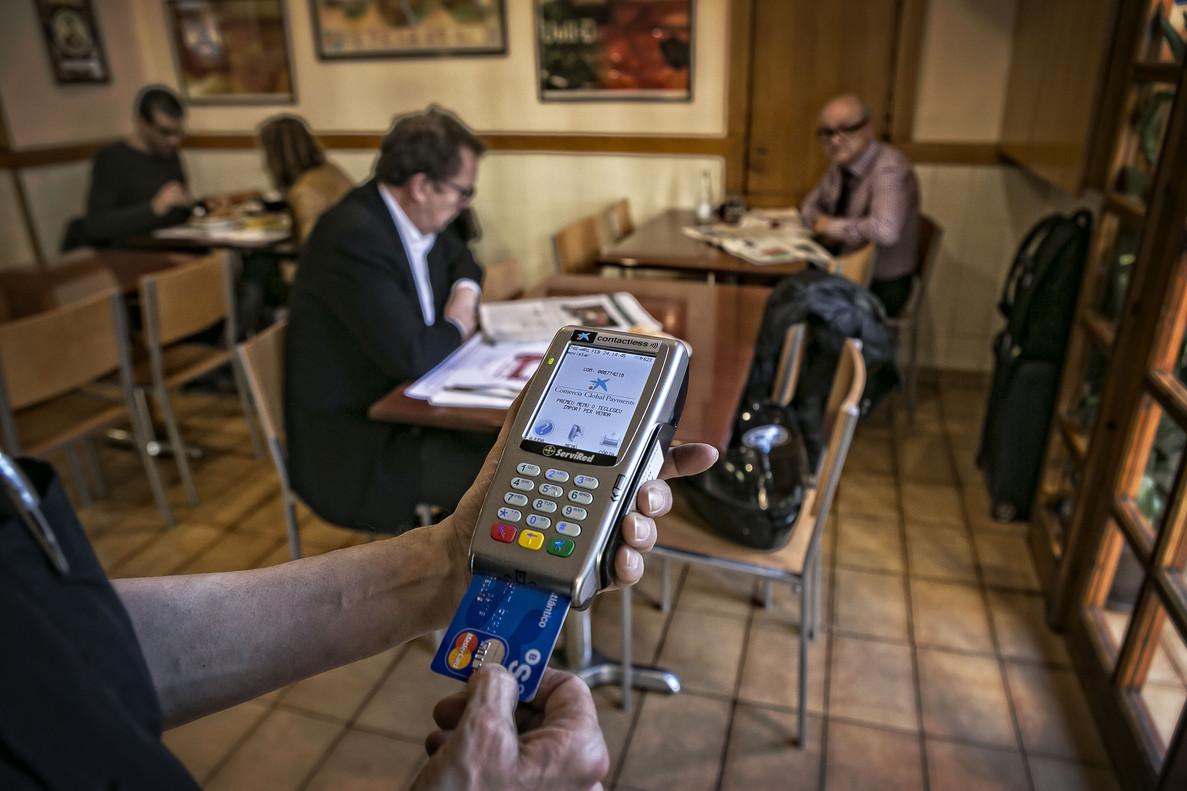 Un camarero cobra con un datáfono a un cliente de un bar de Barcelona.