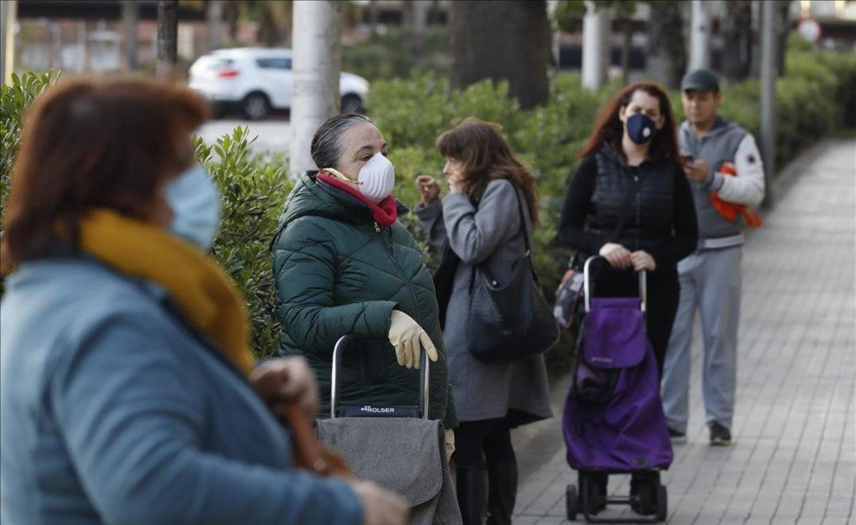 Clientes con mascarilla en la cola de un supermercado en el paseo de la Zona Franca.