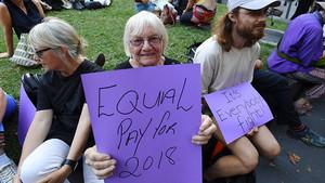 Una australiana pide igual salario para mujeres y hombres, junto a un joven que subraya que es una lucha de todos, en la concentración del Día de la Mujer en Melbourne.