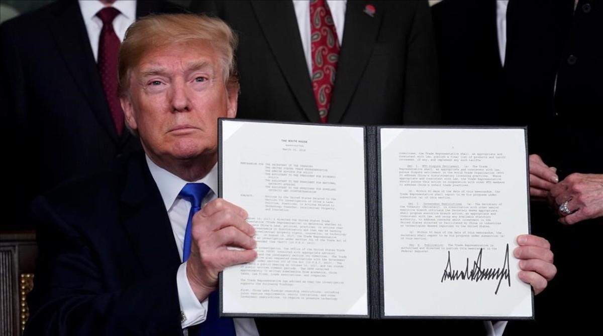 Donald Trumpo muestra su firma en el mermorándum sobre China.