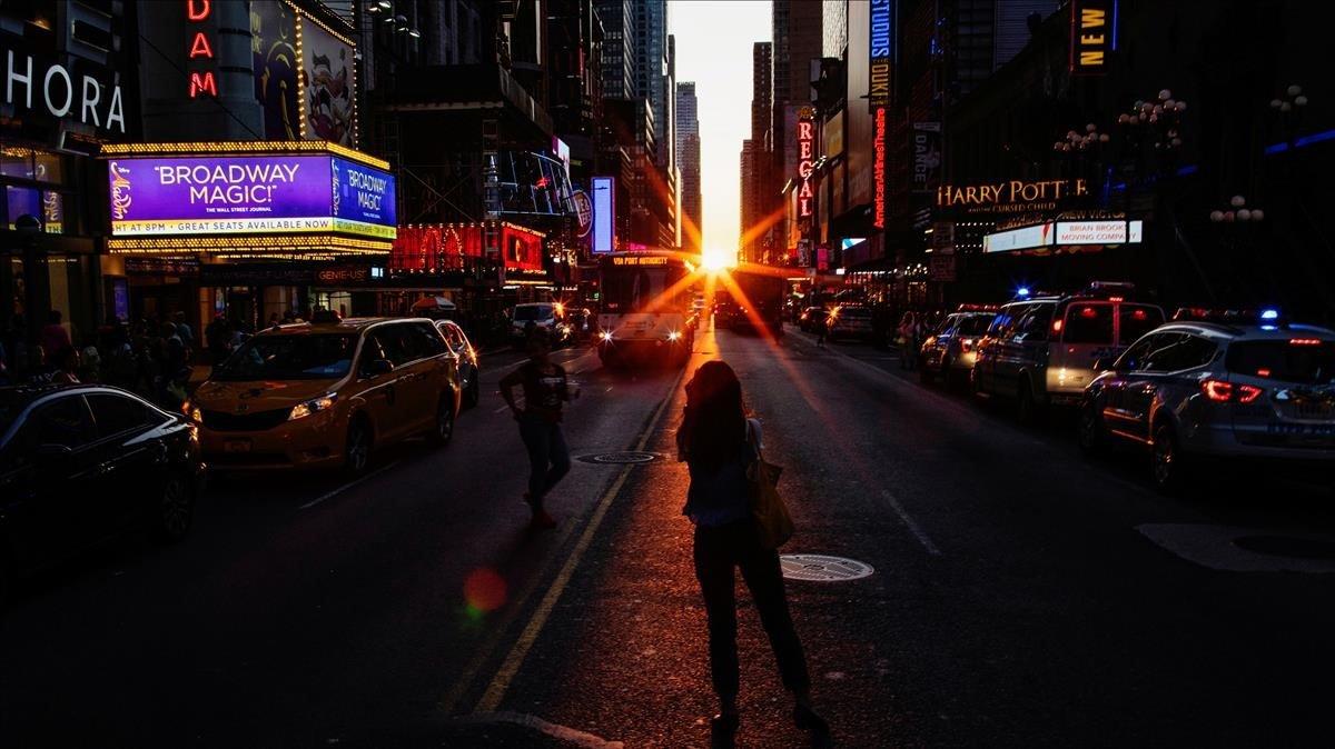 Gente tomando fotografías de la puesta de sol sobre Manhattan alineada exactamente con las calles, esun fenómeno conocido como Manhattanhenge en Times Square en la ciudad de Nueva York.