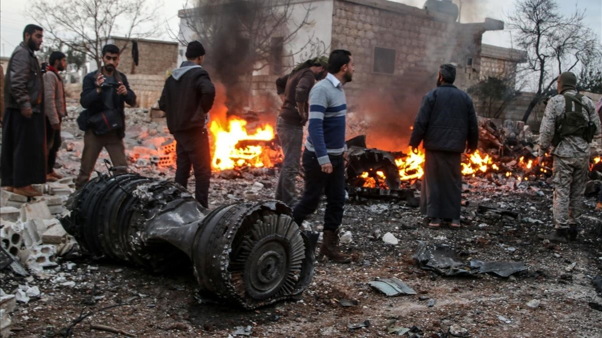 Un grupo de sirios deambula entre los restos del avión ruso derribado.