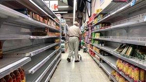 Un hombre camina entre estantes vacíos en un supermercado de Buenos Aires, este domingo.