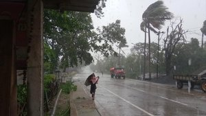 Un hombre se protege de la lluvia y el viento cerca de la localidad india de Dhamra, ante la inminente llegada del ciclón.