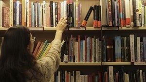 Una mujerconsultala estantería de libros de autoayuda en una librería