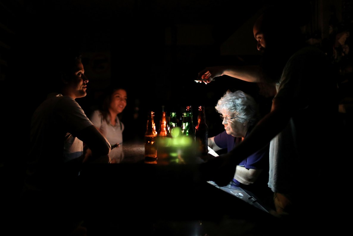 A man uses a cellphone to illuminate a vendor in a bar during a blackout in Caracas Venezuela July 22 2019 REUTERS Manaure Quintero TPX IMAGES OF THE DAY