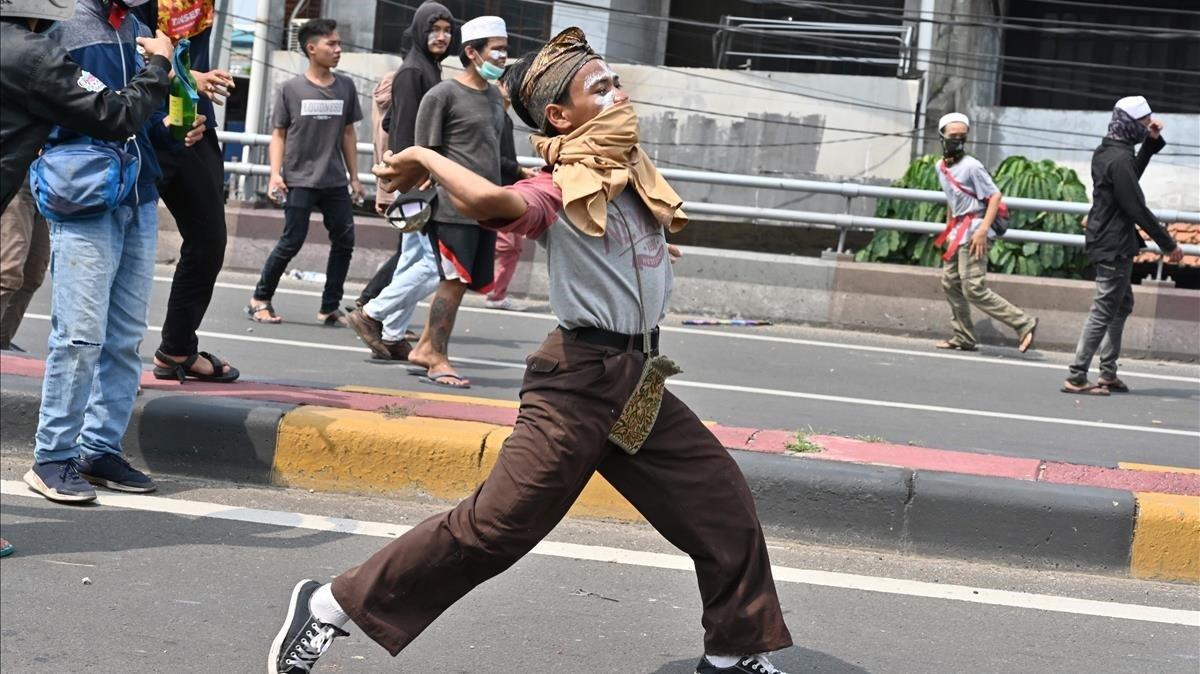 Un manifestante lanza una piedra durante los disturbios de este miércoles en Yakarta.